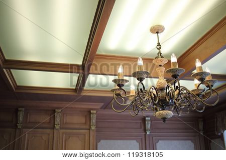 A beautiful chandelier with candlesticks in the interior of the room in the English style