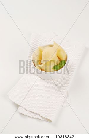 bowl of cooked pasta shells on white place mat
