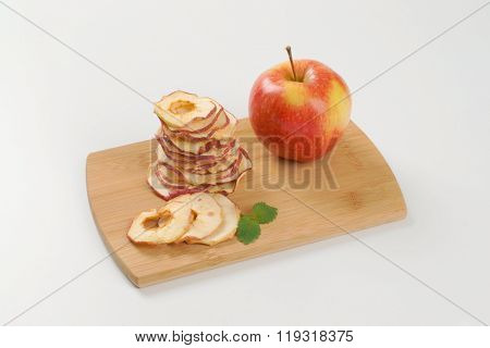 stack of dried apple chips and fresh apple on wooden cutting board