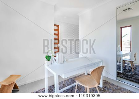 Workroom With White Walls And A Table With Simple Decoration