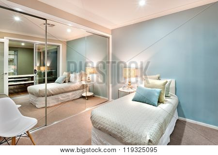 Small Bedroom With Pillows On The A Single Bed And Lights Turned On At Night