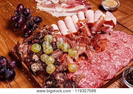 Cold Meat Plate, Slices Prosciutto, Ham,beef Jerky,sausage, Salami With Grapes And Spice On Wooden C