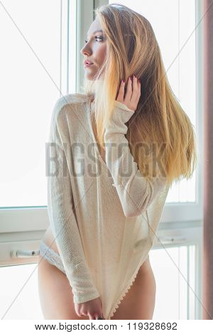 Young sexy blonde girl in panties and sweater standing next to window