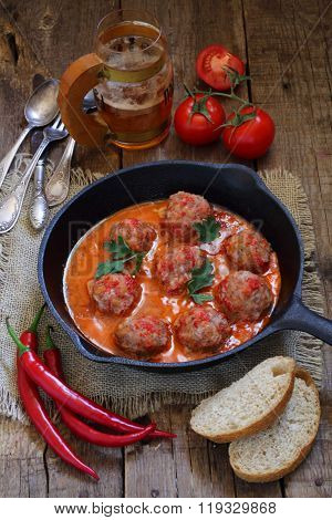 Meatballs In Tomato Sauce With A Garnish From A Spaghetti And Beer In A Transparent Mug