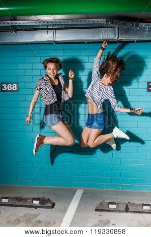 Happy Young People Having Fun And Jumping In Front Of Blue Brick Wall