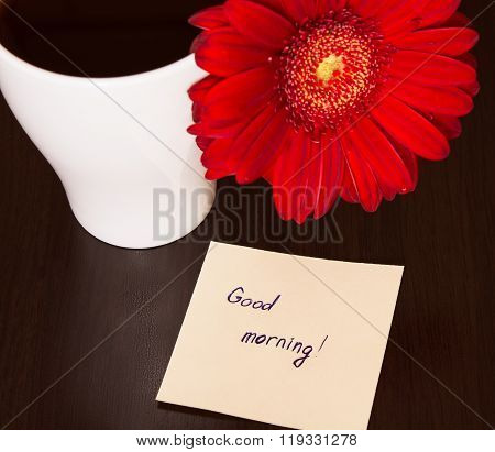 Red Gerbera Flower, Cup Of Coffee And Paper With Text ''good Morning!