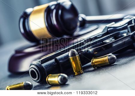 Judge's hammer gavel. Justice and gun. Justice and the judiciary in the unlawful use of of weapons