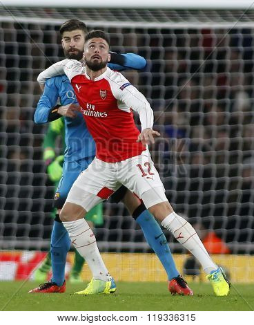 LONDON, ENGLAND - FEBRUARY 23: Gerard Pique of Barcelona and Olivier Giroud of Arsenal compete for the ball during the Champions League match between Arsenal and Barcelona at The Emirates Stadium
