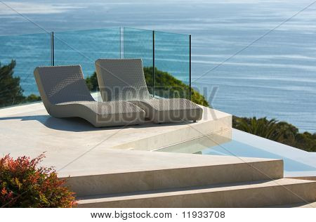 Custom Luxury Pool and Chairs Abstract Overlooking the Ocean