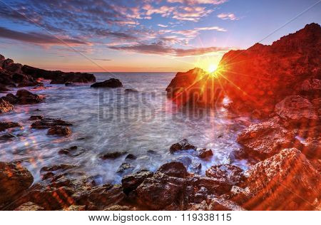 Sunrise on rocky shore and dramatic sky clouds