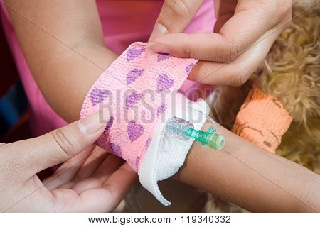 Girl having bandage put around catheter