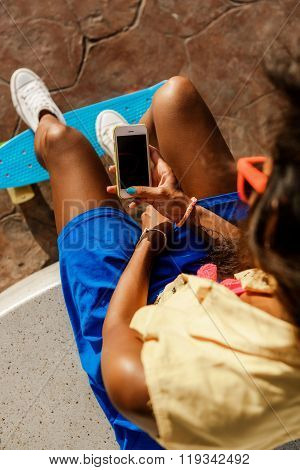 Beautiful Teenage Black Girl In Blue Skirt Sit With Her Smartphone.
