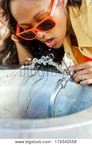 Beautiful Teenage Black Girl In Sunglasses Drinking From Water Drinking Fountain.