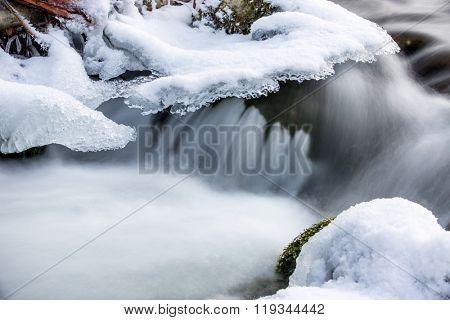 run of winter brook among frozen stones