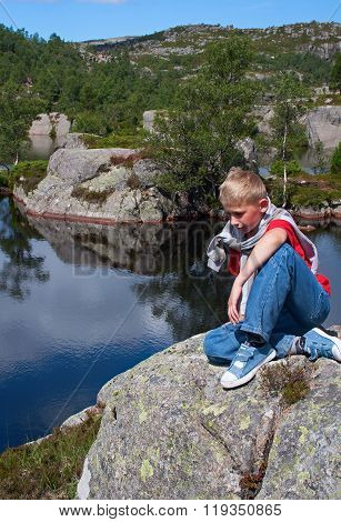 Norway. The Thoughtful Boy Sits On A Big Stone At Water