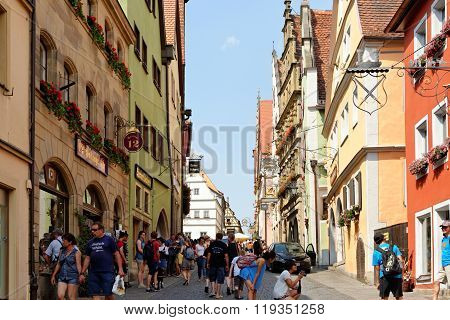 ROTHENBURG OB DER TAUBER GERMANY - AUGUST 10 2015: Schmiedgasse street leading to the central square Marktplatz (Market place). Rothenburg is one of the best-preserved medieval towns in Europe.