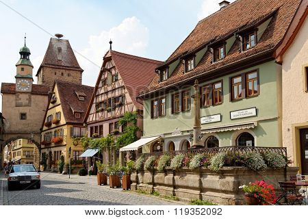 ROTHENBURG OB DER TAUBER GERMANY - AUGUST 10 2015: Rodergasse street with Markus Tower and Roder arch with its slim clock tower which were part of the town's first fortifications (1200).