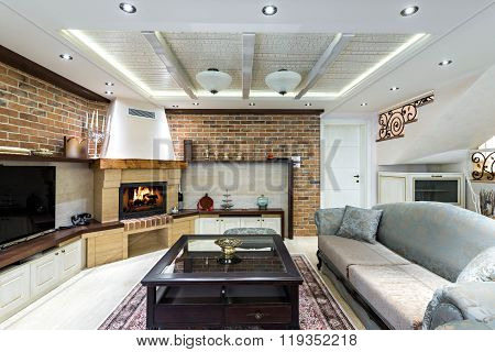 Specious livig room interior with fireplace and brick wall