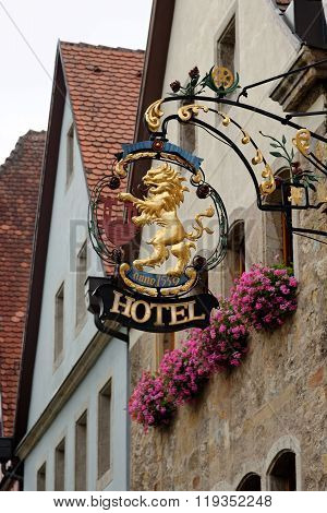 ROTHENBURG OB DER TAUBER GERMANY - AUGUST 10 2015: A hotel wrought iron hanging sign in Rothenburg one of the best-preserved medieval towns in Europe part of the famous Romantic Road tourist route