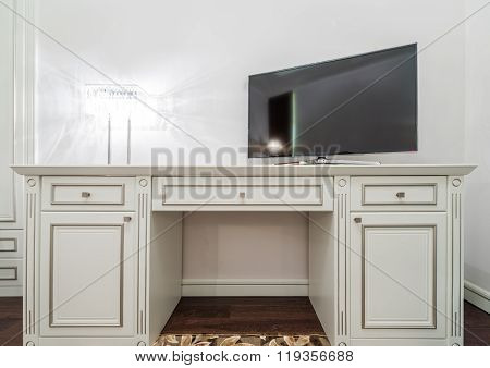 Large black widescreen TV set on the white dresser in a bright room