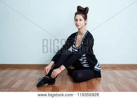 Ballet.  Portrait Of A Teenage Girl With Bow- Knot Hairdo Sitting On The Floor