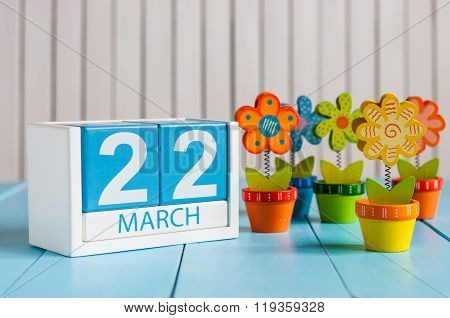 March 22nd. Cube calendar for march 22 on wooden surface with colour flower. Spring concept
