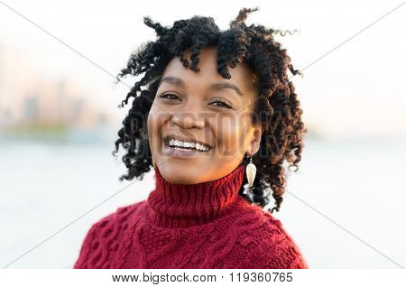 Close up portrait of an african woman standing at river side during sunset. Portrait of happy young african looking at camera. Smiling african woman posing for camera outdoor.