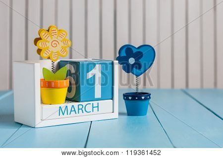 Hello March. Cube calendar for march 1st on wooden surface with colour flower. First spring day 1, c