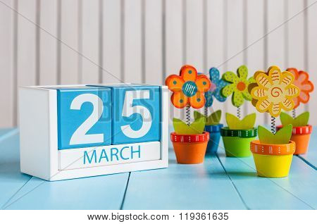 March 25th. Cube calendar for march 25 on wooden surface with colour flower. Spring concept