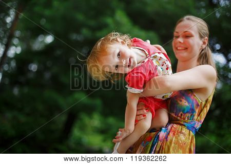 Young mother with her little babyin the garden