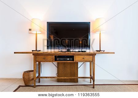 Flat screen TV at wooden shelf in apartment interior