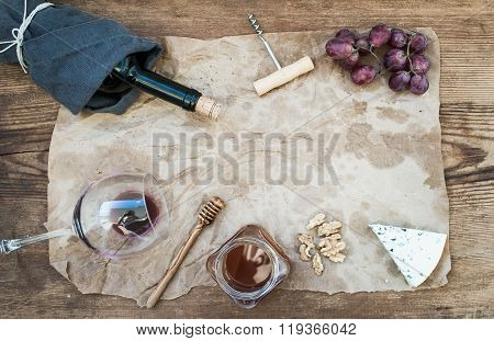 Wine and appetizer set with copy space in center. Glass of red wine, bottle, corkscrewer, blue chees
