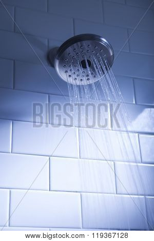 Shower head with water stream on blue background