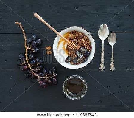 Healthy breakfast set. Bowl of oat granola with yogurt, fresh grapes, almond and  honey over black w