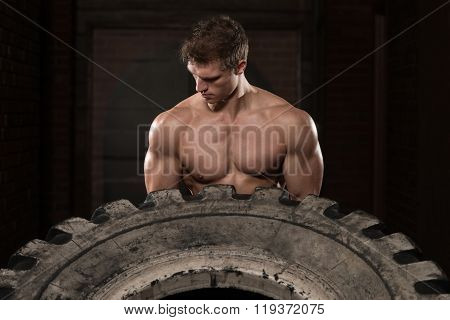 Muscular Man Exercising Crossfit Workout By Tire Flip