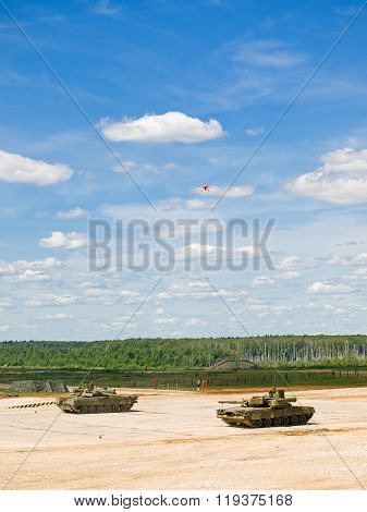 T-80 tanks point each other a gun. Above them flies a drone