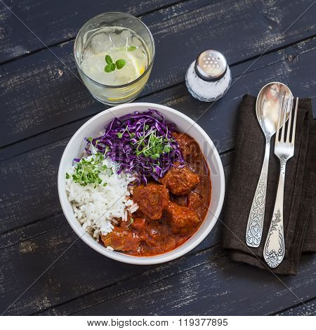 Stewed Meat In Tomato Sauce, Rice, Red Cabbage And Homemade Lemon Lemonade On A Dark Wooden Table. D