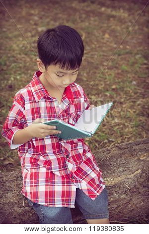 Asian Boy Reading A Book. Education Concept. Vintage Style.