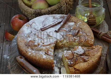 Charlotte With Apples, Cinnamon And Honey On A Wooden Table
