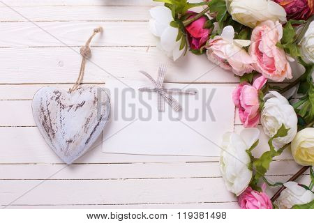 Flowers In Pink Colors With  Decorative Heart  And Empty Tag On White Wooden Background.