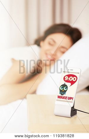 Young woman waking up with mobile alarm clock