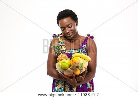 Cute lovely african american young woman in colorful sundress holding glass bowl with different fruits over white background