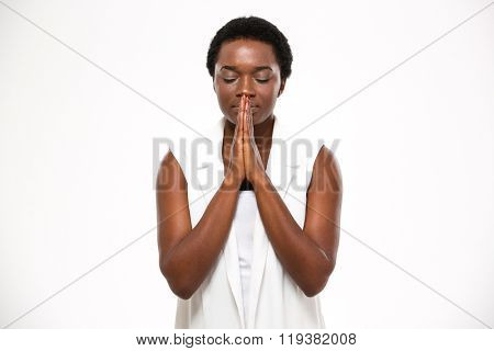 Peaceful beautiful african american young woman standing and praying over white background