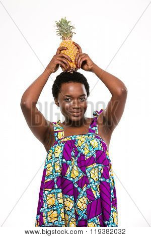 Pretty happy african american young woman in bright sundress holding pineapple on her head over white background