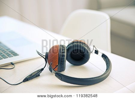 Headphones and laptop on white table against defocused background