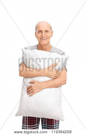 Vertical shot of a senior man holding a pillow and looking at the camera isolated on white background