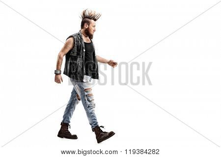 Full length profile shot of an angry male punk rocker walking isolated on white background