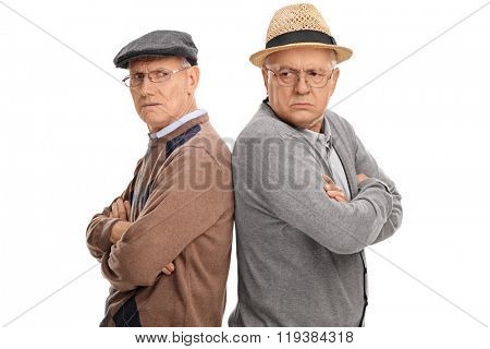 Two seniors angry with each other standing back to back isolated on white background