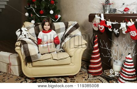 Child Girl On Armchair With Christmas Gift