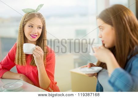 Portrait of teenager girls sitting at the table in the cafe, having fun together, selective focus